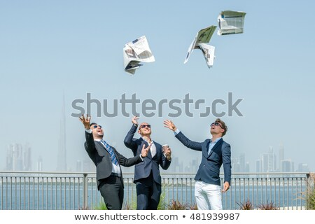 Businessman with newspaper throwing up hands Stock photo © lovleah