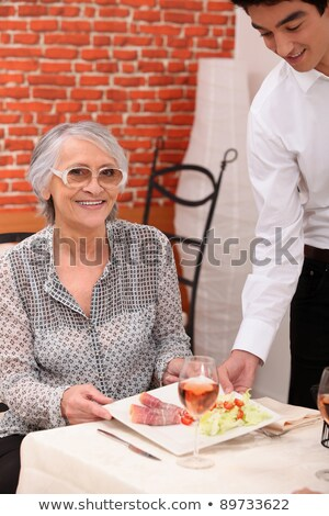 Young waiter serving an older woman in a restaurant Stock photo © photography33