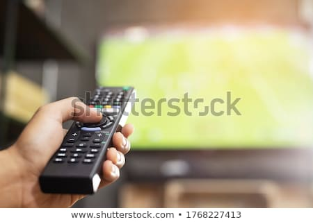 TV monitor, keyboard and hand with remote control Stock photo © ABBPhoto
