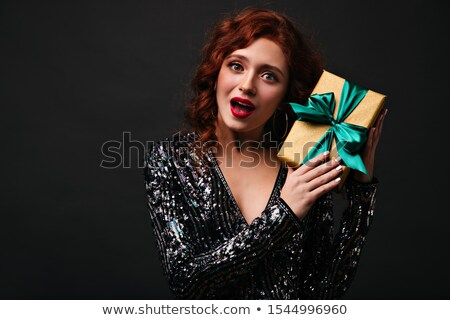 attractive lady in red attire with xmas gift stock photo © stockyimages