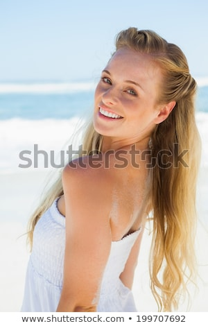 Blonde in white dress smiling at camera on the beach Stock photo © wavebreak_media