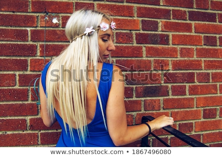 Woman in blue dress against a brick wall Stock photo © filipw
