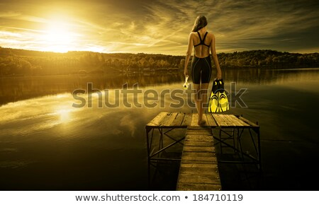 Woman in black swimwear standing on pier at sunset Stock photo © deandrobot