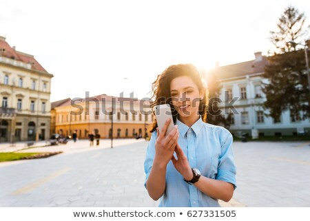 Portrait of cute young woman using cellphone in the street. Stock photo © deandrobot