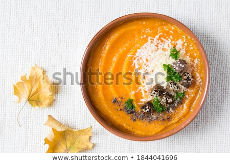 Pumpkin cream soup with parmesan toast in a white plate. Pumpkin stock photo © d_duda