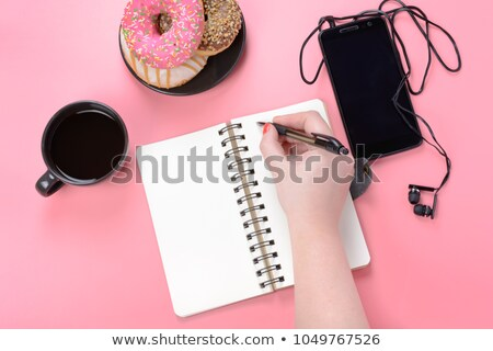 Pink donut in a woman's hand on black background stock photo © Sibstock