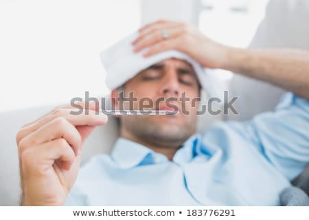 Sick man checking his temperature Stock photo © wavebreak_media