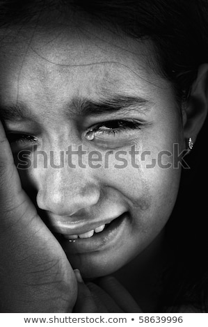 Stock photo: Crying girl, tears on cheeks, low light key, added grain, black and white
