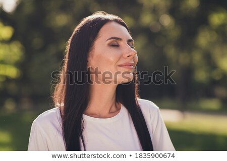 Cheery young girl relaxing at the park outdoors Stock photo © deandrobot