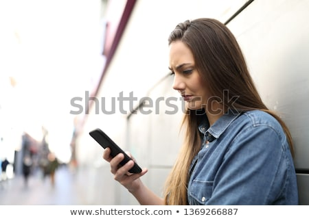 Stock photo: Anxious woman using phone on street