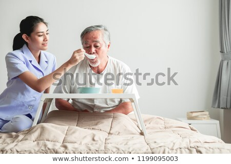 Caretaker Feeding Senior Man Stock photo © AndreyPopov