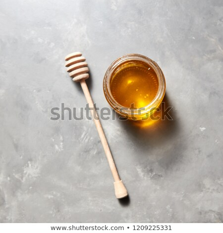 Sweet flower natural honey in a jar and wooden spoon on a gray concrete table. Top view. Jewish New  Stock photo © artjazz