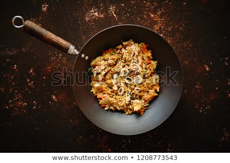 traditional orginal fried spicy rice with chicken served in a round iron wok stock photo © dash