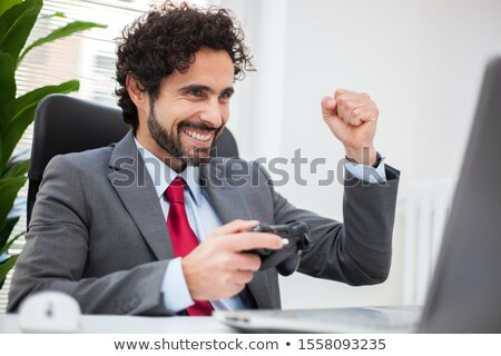 Businessman playing videogames in his office Stock photo © Minervastock
