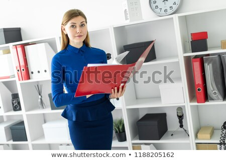 A young girl stands in the office near the shelter and holds a folder with documents in her hands. Stock photo © Traimak