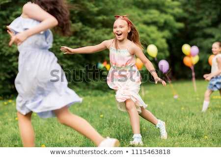 happy kids playing tag game at birthday party stock photo © dolgachov