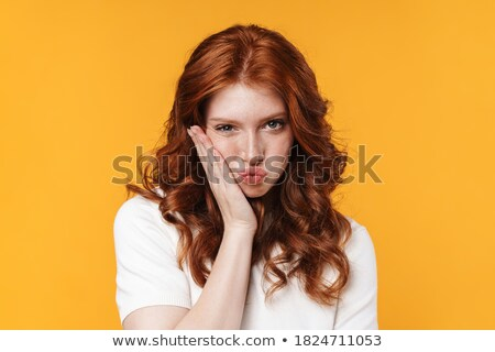Displeased woman with toothache isolated over yellow background. Stock photo © deandrobot