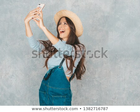 Image of stylish curly woman 20s smiling and taking selfie photo Stock photo © deandrobot