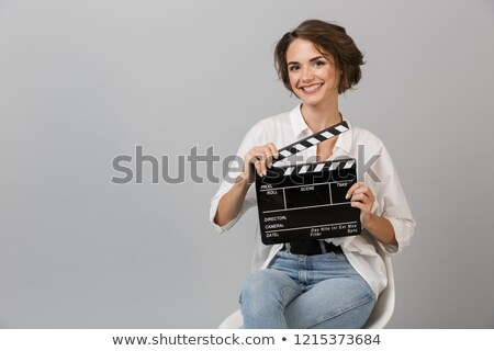 Business woman posing isolated holding clapper board. Stock photo © deandrobot