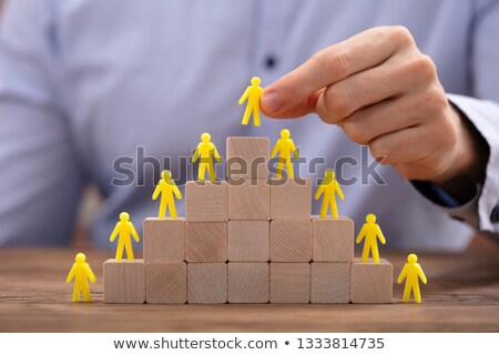 Person Placing Yellow Human Figure On Top Of Stacked Blocks Stock photo © AndreyPopov