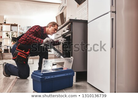 Stock fotó: Technician In Overall Fixing Oven In Kitchen
