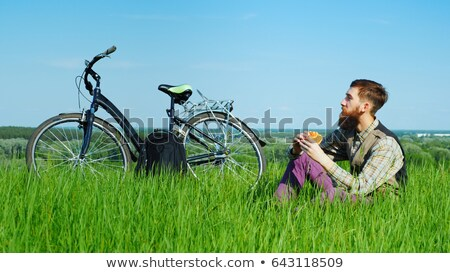 young man eating a hamburger in the park stock photo © galitskaya
