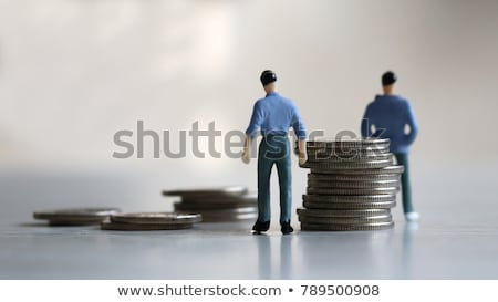 miniature man and woman on two piles of coins Stock photo © nito