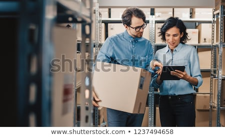Woman and man as workers in logistics center using computer Сток-фото © Kzenon