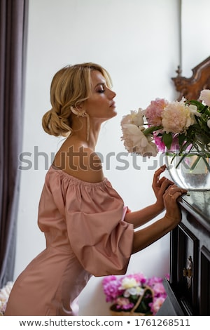Foto stock: Woman Admiring Beauty of Hyacinth Pink Flower
