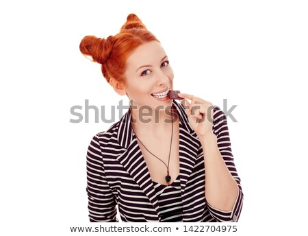 Happy young redhead woman eating chocolate. Looking camera. Stock photo © deandrobot