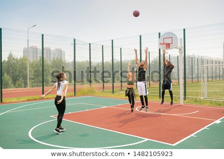 Team of young intercultural friends or students working out on basketball court Stock photo © pressmaster