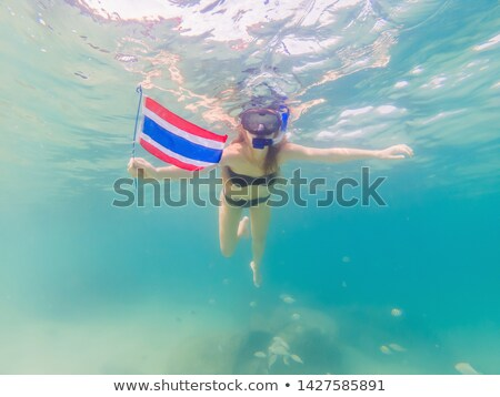 Happy woman in snorkeling mask dive underwater with tropical fishes with thailand flag in coral reef Stock photo © galitskaya