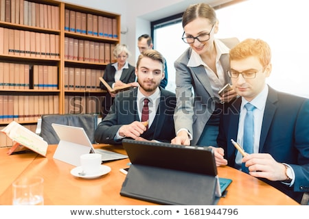 Lawyers in their law firm working on computer with books in background Stock photo © Kzenon