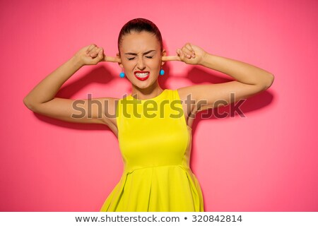 Stock photo: Young woman standing with fingers in her ears