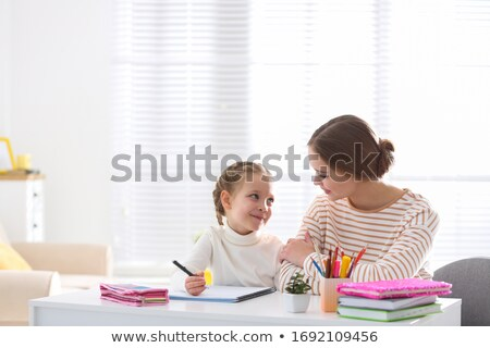 Mother helping girl to do homework stock photo © cwzahner