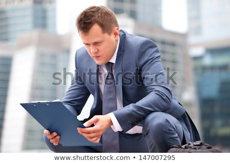 Businessman sitting on his haunches Stock photo © cherezoff