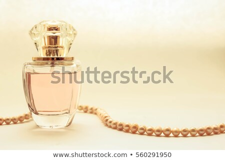 Perfume in a glass bottles and pearl beeds stock photo © caimacanul