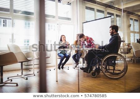 Businessman on wheelchair with photo editors in meeting room Stock photo © wavebreak_media