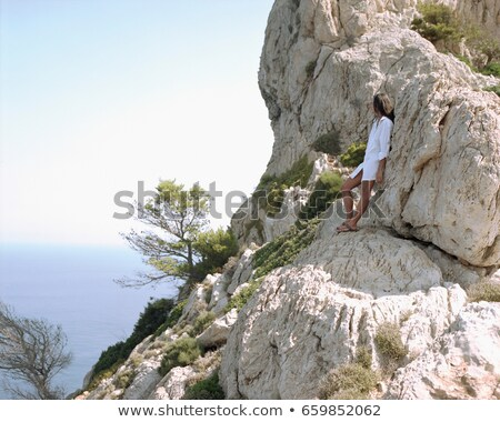 Woman leaning on large rocks looking out over the sea. Stock photo © IS2