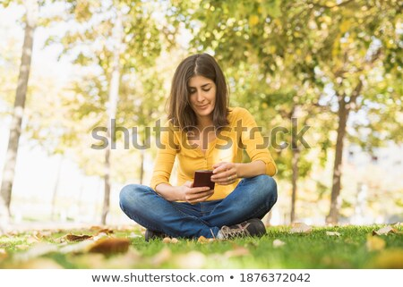 young sports woman outdoors sitting on grass using phone stock photo © deandrobot