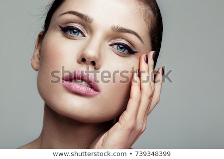 Beautiful young woman with bright makeup and pink lips make a kiss holding your finger near the . Hi Stock photo © studiolucky