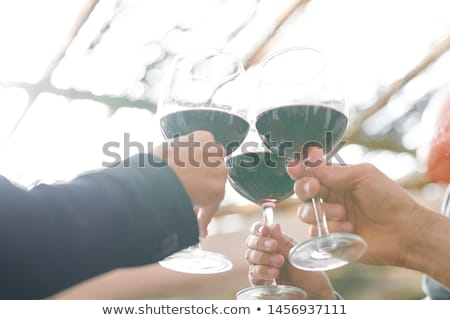 Hands of several friends clinking with wineglasses of bordo cabernet Stock photo © pressmaster