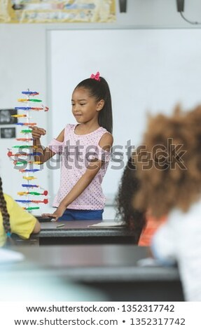 Front view of mixed -race schoolgirl looking at a DNA model in classroom at elementary school Stock photo © wavebreak_media