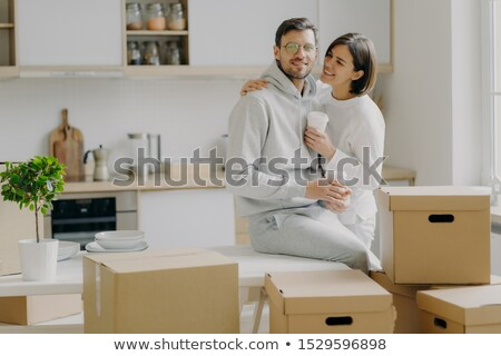 Caring woman embraces husband with love, drink takeaway coffee, pose in modern kitchen with unpacked Stock photo © vkstudio