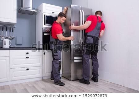Two Male Movers Placing The Refrigerator Stock photo © AndreyPopov