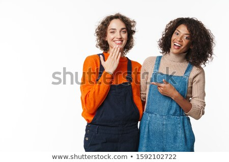 Portrait of two laughing women hugging and pointing finger Stock photo © deandrobot