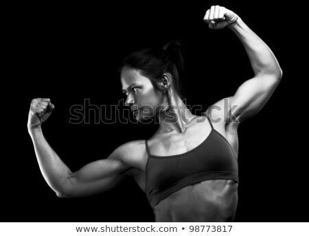 Muscular female body against black background Stock photo © Nobilior