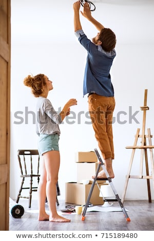 young woman on ladder changing bulb Stock photo © photography33