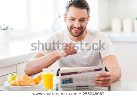 Stock photo: Young man having coffee and reading newspaper