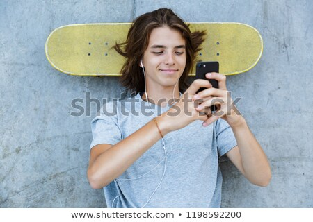 Cheerful young teenge boy spending time at the skate park Stock photo © deandrobot
